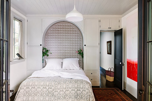 Bedroom with built in tufted arch headboard