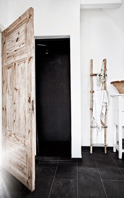 White bathroom with rustic wood door and black tile floor in Jenny Hjalmarsson Boldsen's home