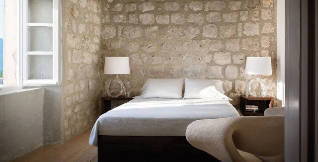 bedroom bed minimalist decor interior design croatian croatia home coastline coast villa interior exposed limestone walls white furniture home furnishings