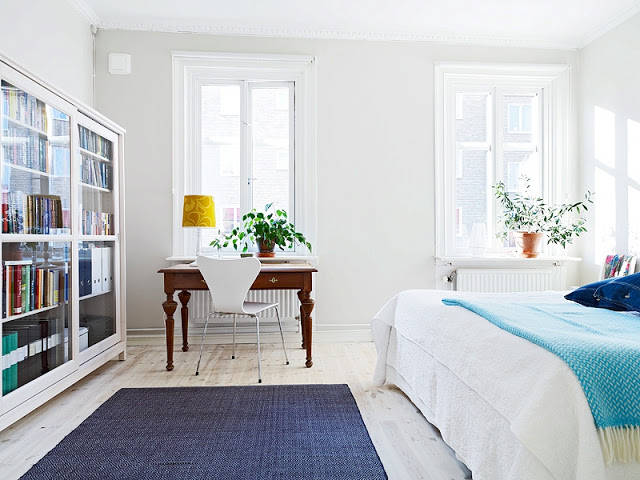 Simple bedroom in a tiny apartment with a desk and arne jacobsen series 7 chair, large bed, blue rug, and built in book shelf with glass door