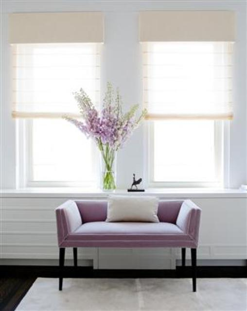 A lavender settee below two windows with a white accent pillow, on a white rug with dark wood floors
