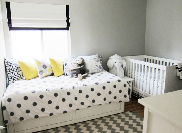 nursery with black and white chevron patterned rug, a twin bed with underbed storage and polka dot bedding, cococozy accent pillows, a white crib and an elephant hamper
