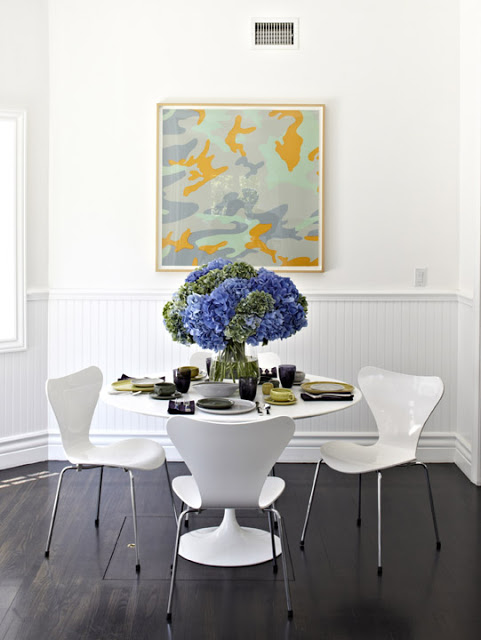 Breakfast nook with dark wood floors, white walls with a framed Andy Warhol Camouflage print, Four 1955 Arne Jacobsen Series 7 Chairs around a 1956 Eero Saarinen Tulip Table.
