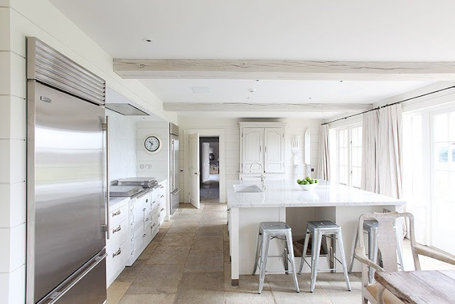 kitchen with white island, metal stools, white cabinets, bottom freezer and french door refrigerator