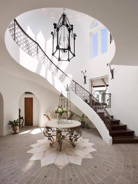 Foyer with two story iron railing stairs, a stone floor with a marble sunburst, a round table with iron work legs and Moroccan inspired iron pendant light
