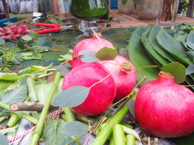 Four fresh pomegranates on a wooden patio table covered with leaves, flowers and other plant scraps