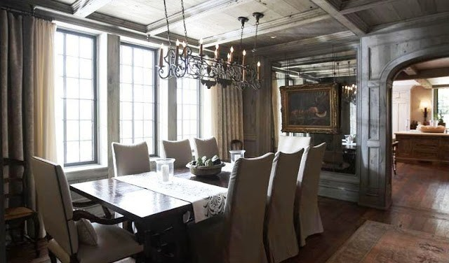 Formal dining room with grey wash wood paneling with exposed beams, encasement windows, neutral floor length curtains, wood floor, a long dark wood table surrounded by upholstered high back chairs and a wire chandelier