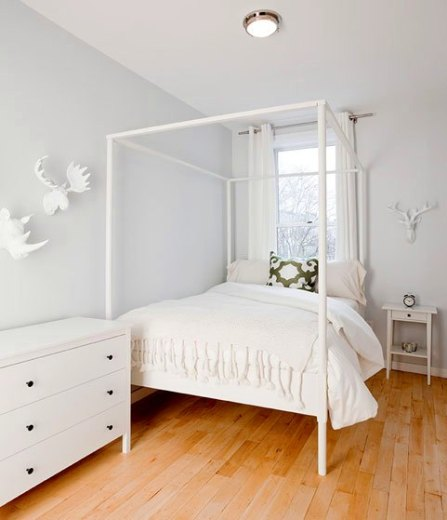 White bedroom with a chest of drawers, canopy bed, and white animal head sculpture, wood floor and a green and white accent pillow