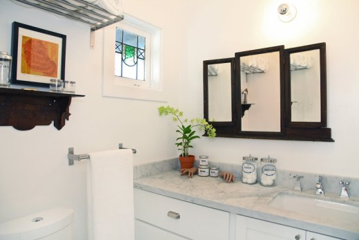 Bathroom with marble counters and a three dark wood mirrors