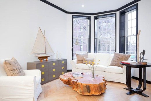 Living room with black trimmed windows, a white sofa and matching armchair, herringbone wood floor, tree trunk coffee table, grey chest of drawers with yellow drawer pulls and a ship on the top and a black table
