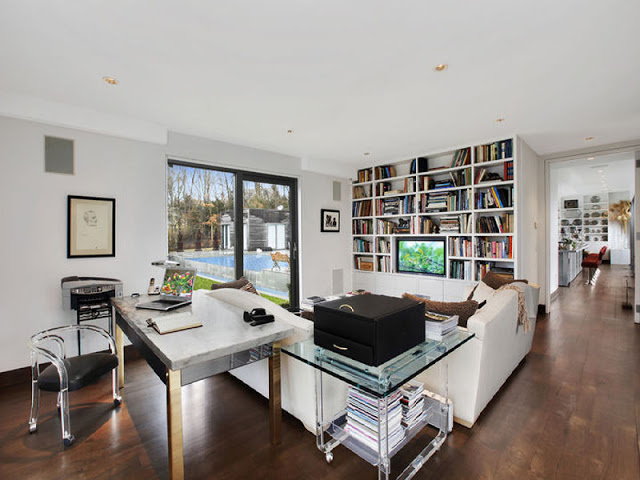 den in the Hamptons with wall sized book shelf, white sofas, wood floors and a glass coffee table