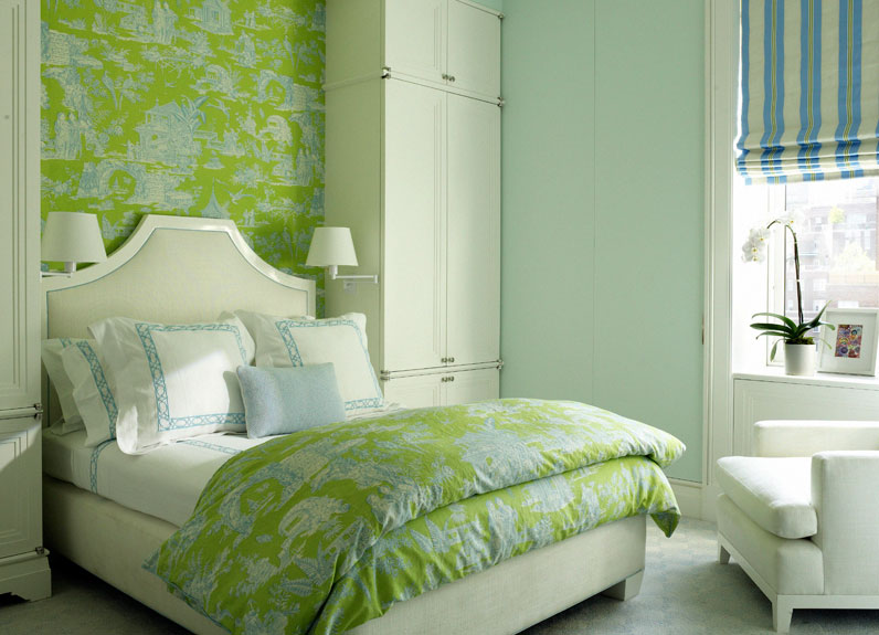 Bedroom With Wall Covered In Green Toile Wallpaper. The Bed Has A Molded  Headboard And