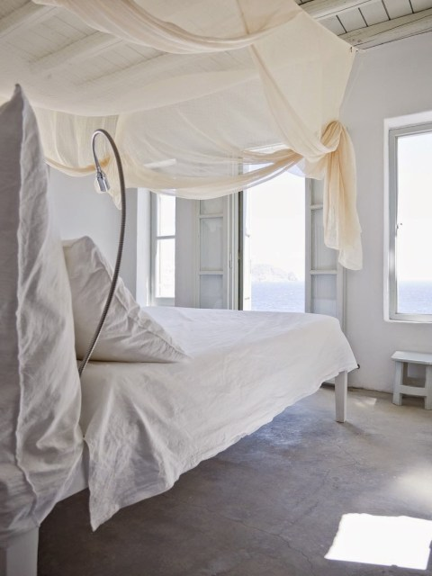 White bedroom with a canopy bed and ocean view by Jerome Galland