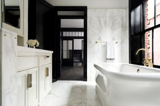 michael mundy's black and white bathroom with white freestanding tub, black lacquer trimed door,  glossy brass faucet pulls, and carrara marble floors, walls and counters