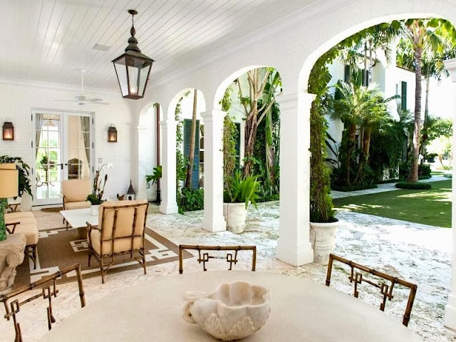 Veranda of a Palm Beach estate with a lantern style pendant light and arched entryways