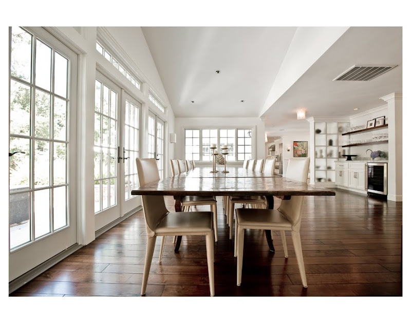 White kitchen with stainless appliances, a wood floor, long wood table and cream colored chairs. The entire room is surrounded by french doors leading outside