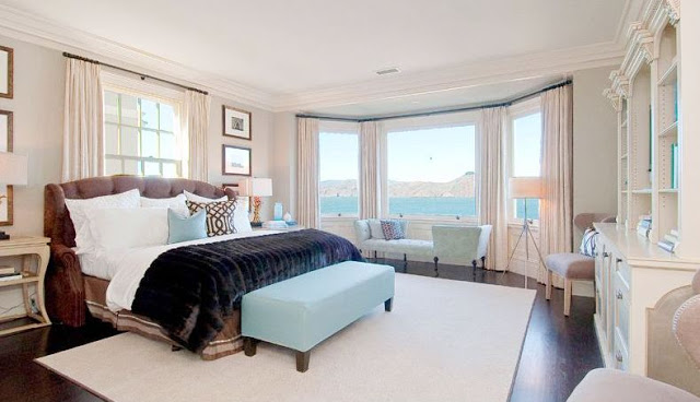 Master Suite with ocean view, dark wood floor, upholstered headboard, floor length curtains, white rug and a light blue ottoman