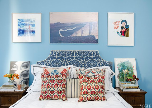 master bedroom with blue walls covered in art, upholstered ikat headboard, and ikat accent pillows