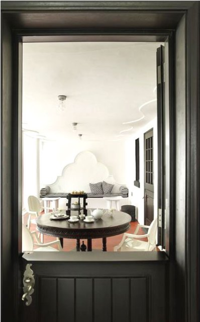 Black door and a white dining area