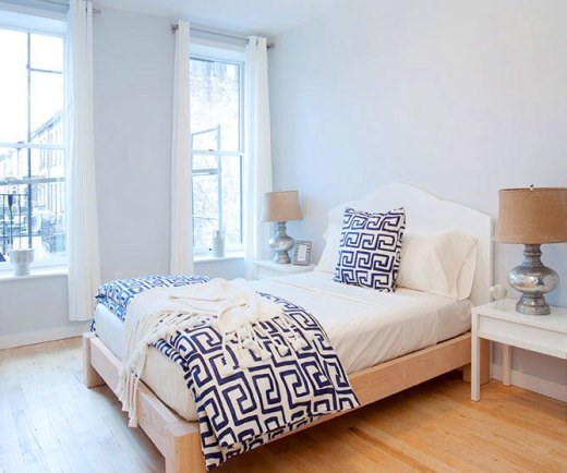 Apartment bedroom with wood floor, light periwinkle walls, white drapes, two white side tables with mercury lamps, the bed is white with a blue and white graphic printed accent pillow and duvet cover