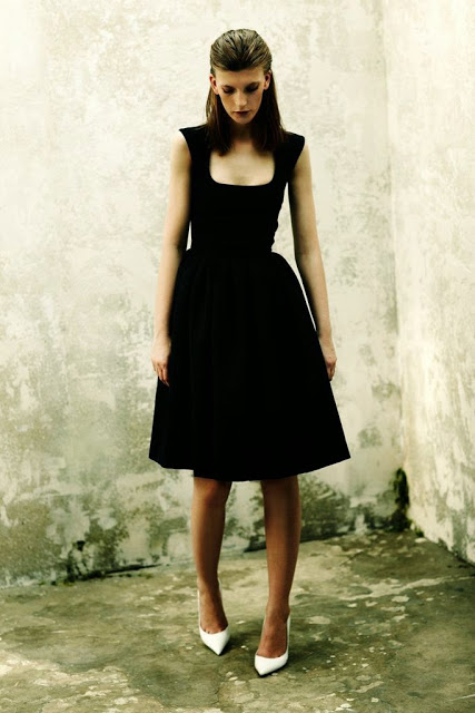 Model wearing black dress and white shoes