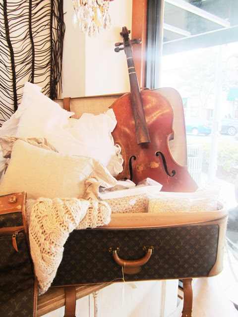 display in Pom Pom with their throws, pillow and a violin in a Louis Vuitton suitcase