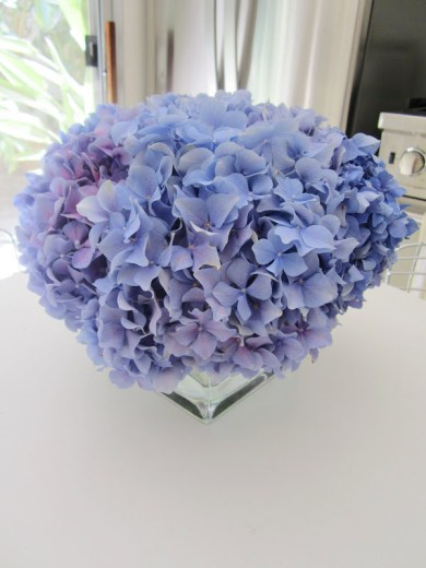 A pave arrangement of purple hydrangea on a white kitchen table