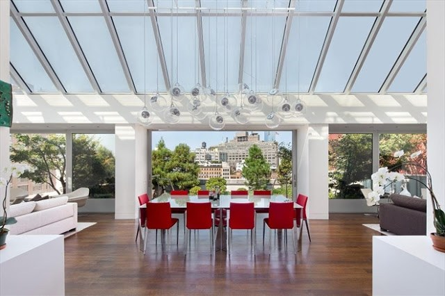 Penthouse in Tribeca with a glass ceiling and large glass windows overlooking a cityscape. A white table is surrounded by red chairs is placed facing the central window
