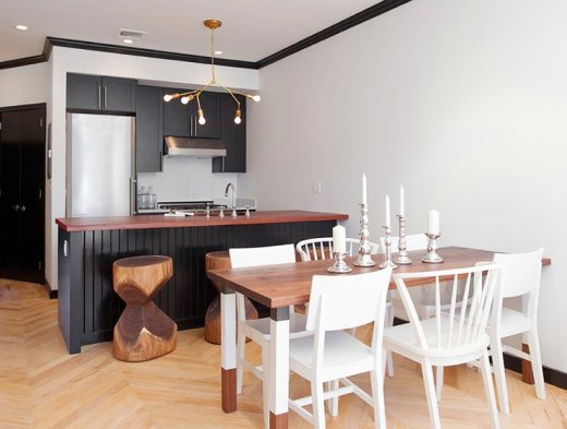 Kitchen and dining area with black cabinets and drawers, stainless appliance, herringbone wood floor, a branch inspired chandelier, a wood table, mismatched painted white wood hairs and carved stools made from tree trunks