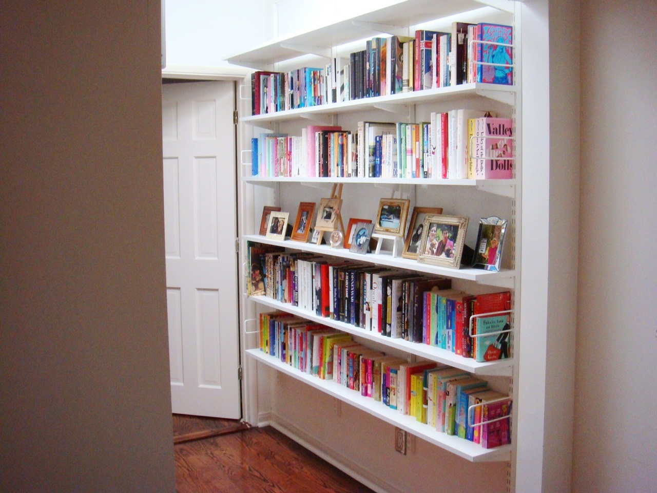 Sleek Light Bright And White Hallway Library Full Of Colorful Books Framed Photos