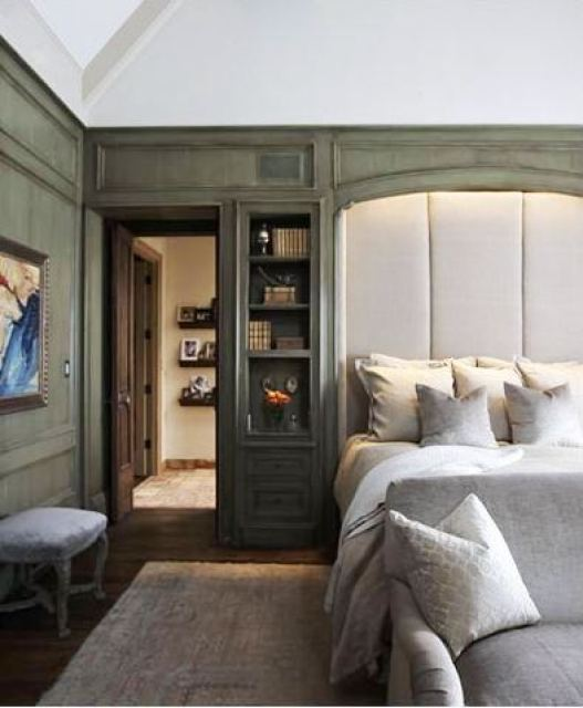Master bedroom with green stained wood paneling and built-in shelving surround an oversized upholstered headboard, at the foot of the bed is a grey sofa with matching accent pillow, the room has dark wood flooring and a large neutral area rug