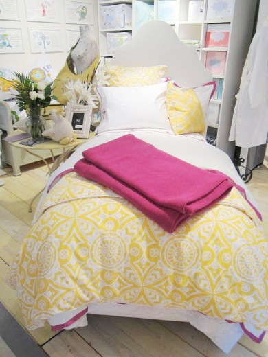 Twin bed by Serena & Lily with yellow graphic print duvet cover and pillows with a splash of fuchsia in the form of a throw and pillow and bed sheet trims