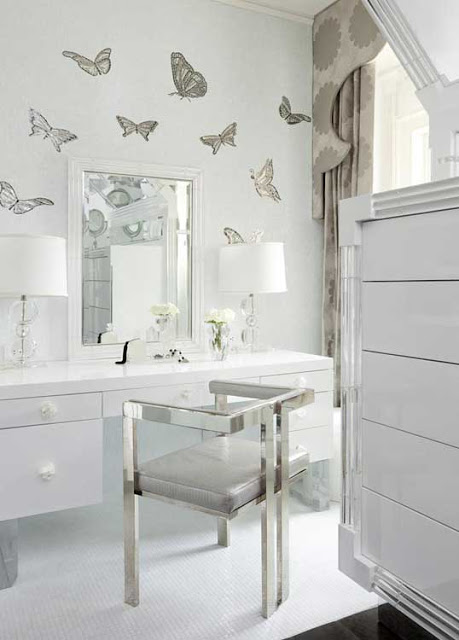 Girly walk in closet with buttery fly wall paper, a vanity, large mirror, stainless chair and white cabinets