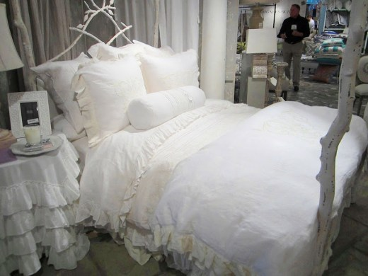 Alternative view of the iron bed frame made to look like tree branches. The bedding is white and very romantic from Pom Pom at Home designed by Hilde Leiaghat.
