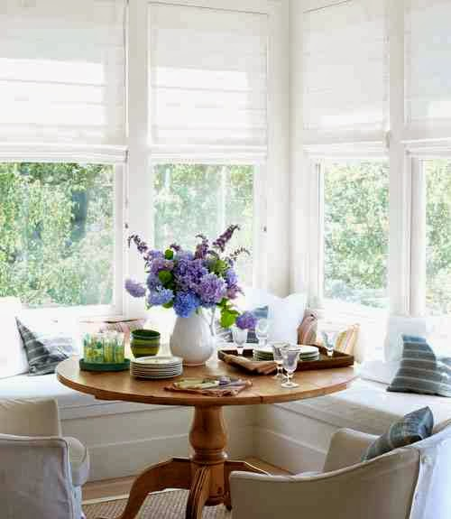 Bright breakfast nook with white roman shades, L-shaped banquette seating and a wood table