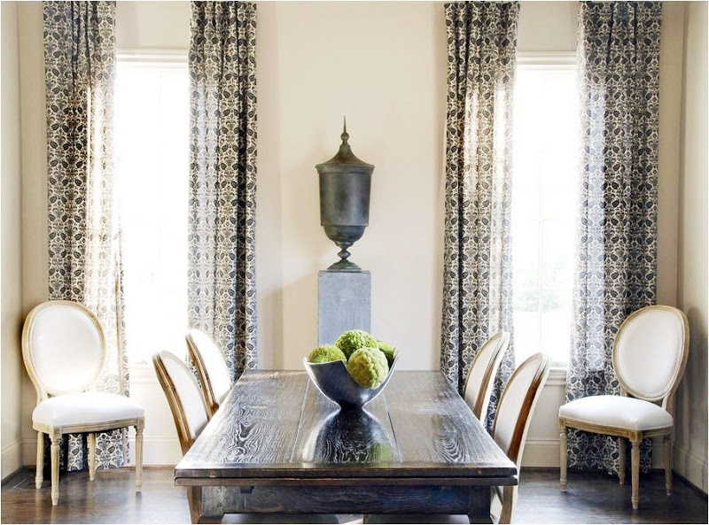 Dining room with high ceilings, classic chairs, long wood table, black urn, dark wood floor and printed curtains