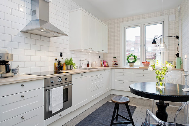 small modern eat in kitchen with plaid walls, louis ghost chairs, round table, white cabinets, window, stainless steel oven, stove top and hood
