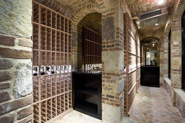 wine cellar with brick walls, wooden racks and brick herringbone floor