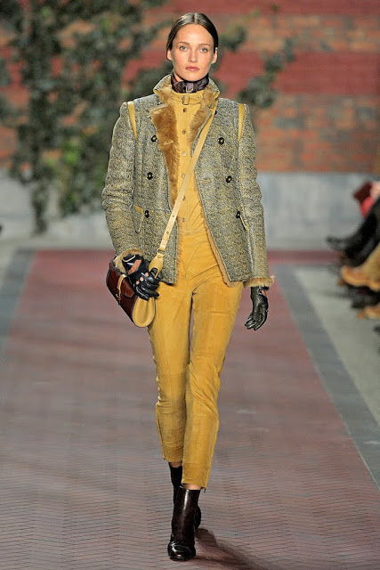 model from tommy hilfiger's fall 2012 runway show wearing mustard yellow pants, a fur lined jacket and boots