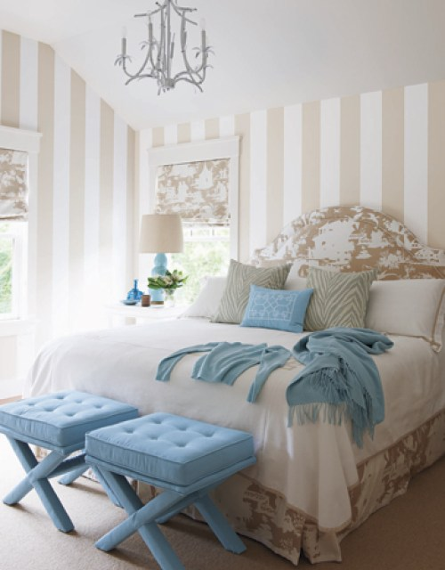 bedroom with upholstered headboard, blue ottomans at the foot of the bed, striped beige and white walls and a chandelier