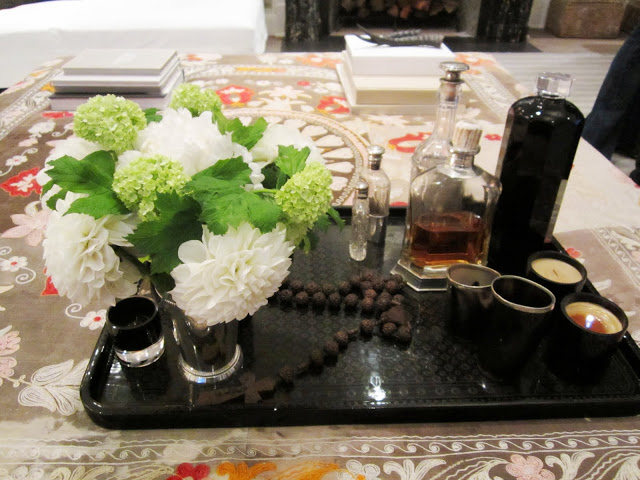 Close up of a black tray on the patterned ottoman. On the tray are prayer beads, candles, assorted bottles and a cup full of white hydrangeas