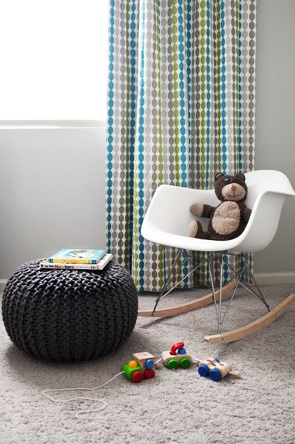 Kid's room with gray carpet, gray braided poof seat, floor length curtains with turquoise, green and gray spots in rows running down it, and a white Eames chair with a teddy bear in it