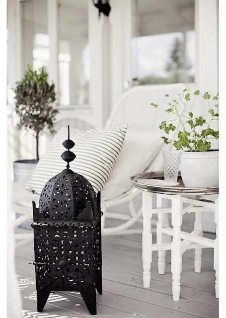 Black Moroccan lantern lamp on a grey front porch