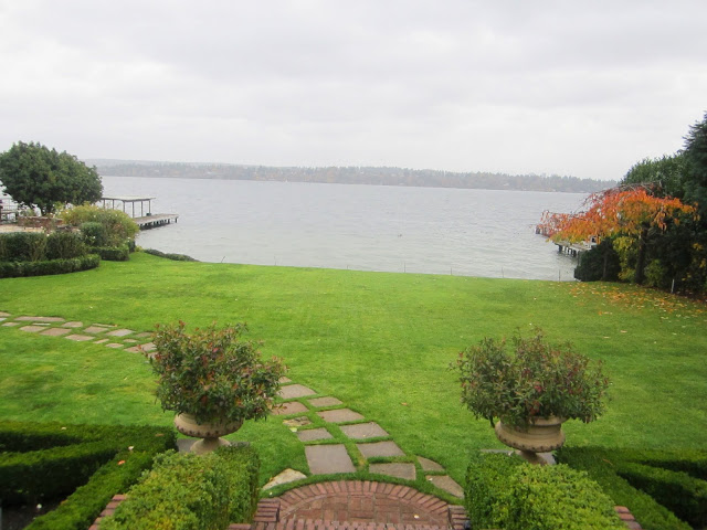 Lake Washington estate with a lake view, grassy yard and a stone path on a cloudy day