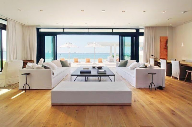 living room with wood floors, white dueling sofas, floor length white curtains, with a large window overlooking the water
