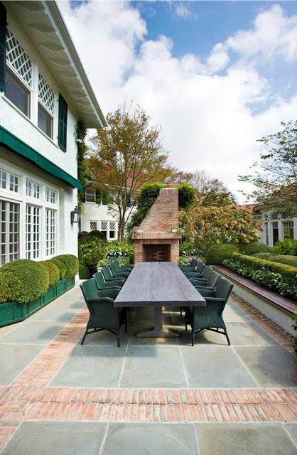 Mansion with a large outdoor table and brick fireplace