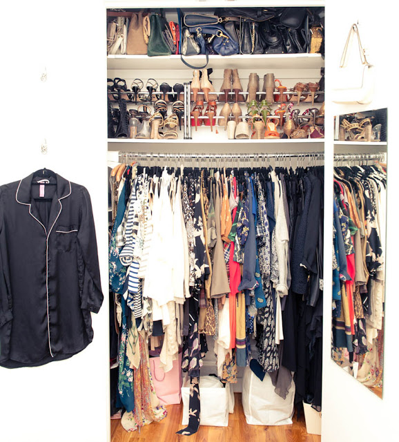 tiny closet stuffed full of clothes with shoe and purse racks on the top shelves
