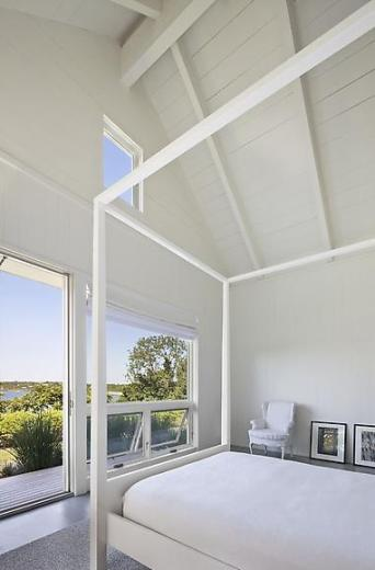 White bedroom in a Montauk on Long Island lake house with high ceilings, a picture window, glass door, wood floor, a white wingback armchair and white canopy bed