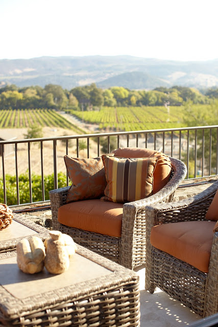 Patio with wicker armchairs with orange cushions and matching wicker coffe table overlooking a vineyard in Napa