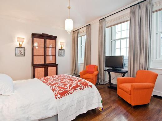 Guest bedroom in a park avenue apartment with orange club chairs, a television, wood floor, encasement windows, and an pendnat light